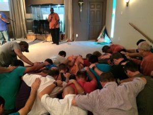Men praying in Brenham